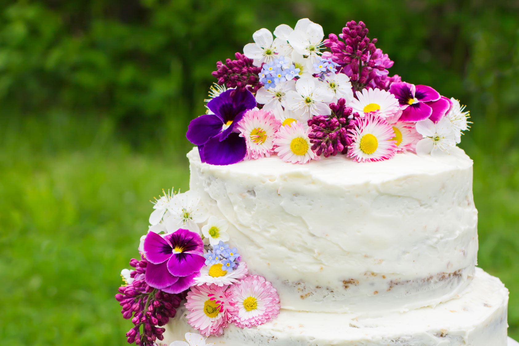 Semi-naked wedding cake with large colourful flowers