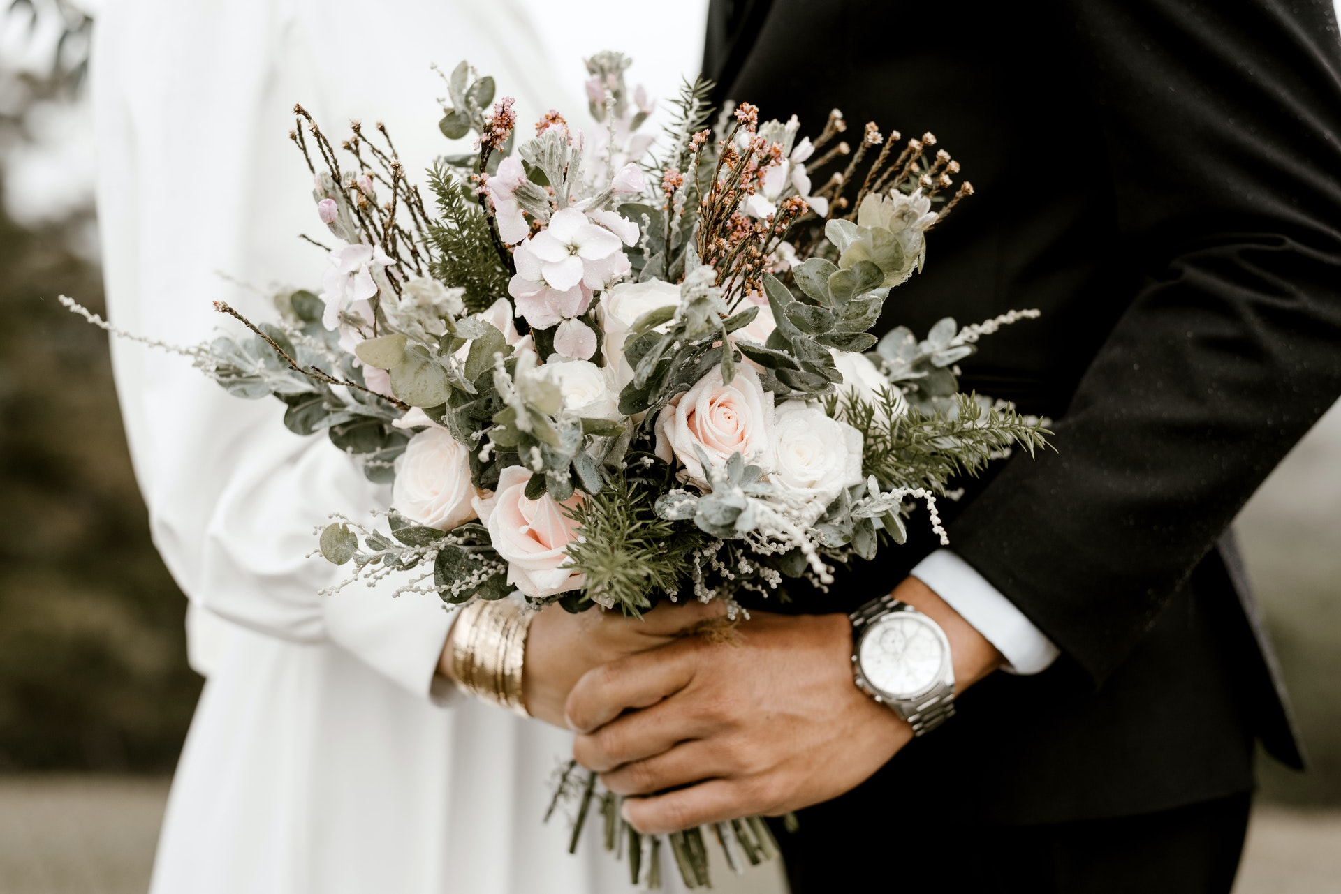 Couple holding flowers together at their wedding